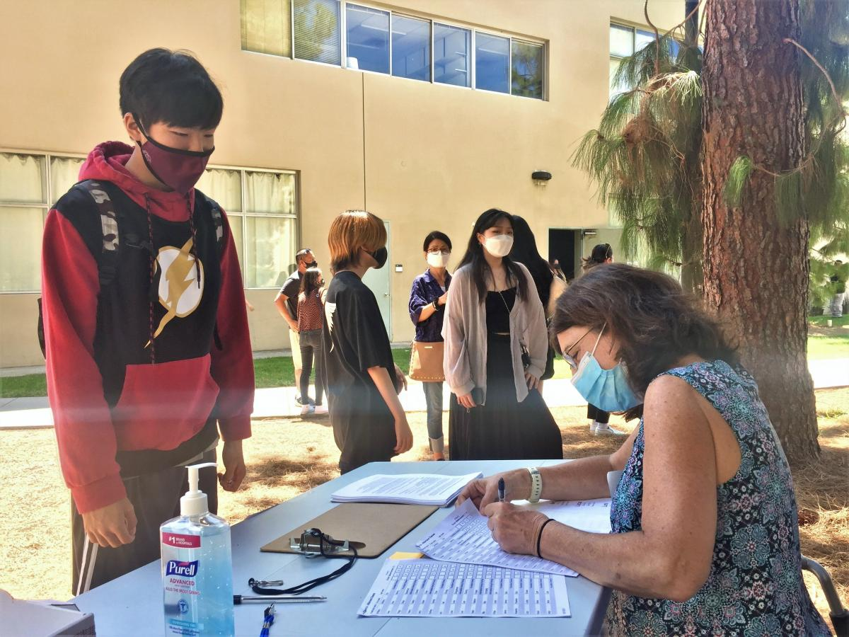 Male student signing-in to Ryman Arts classes at Cal State Fullerton by Executive Director Diane Brigham