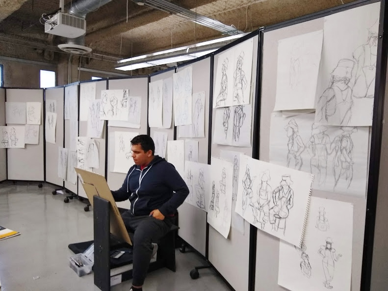 Ryman Arts student Andy R. (Ryman '19) works on his classmates' drawings during a collaborative drawing session