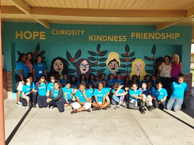 Bunche Middle School Students in front of Herstory mural Commissioned by Global GLOW to celebrate International Day of the Girl,