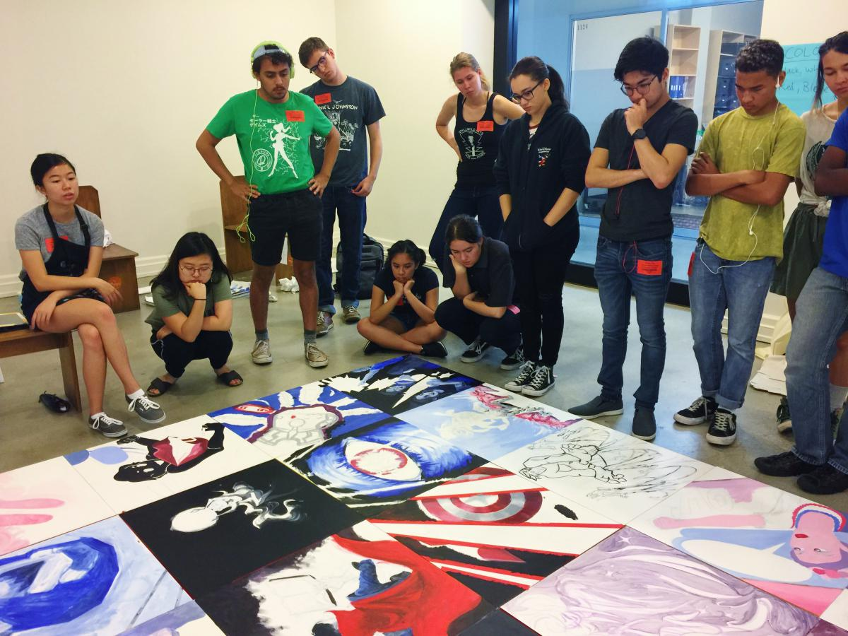 In between painting sessions, participants position their individual panels together in order to provide constructive critiques on the project as a whole
