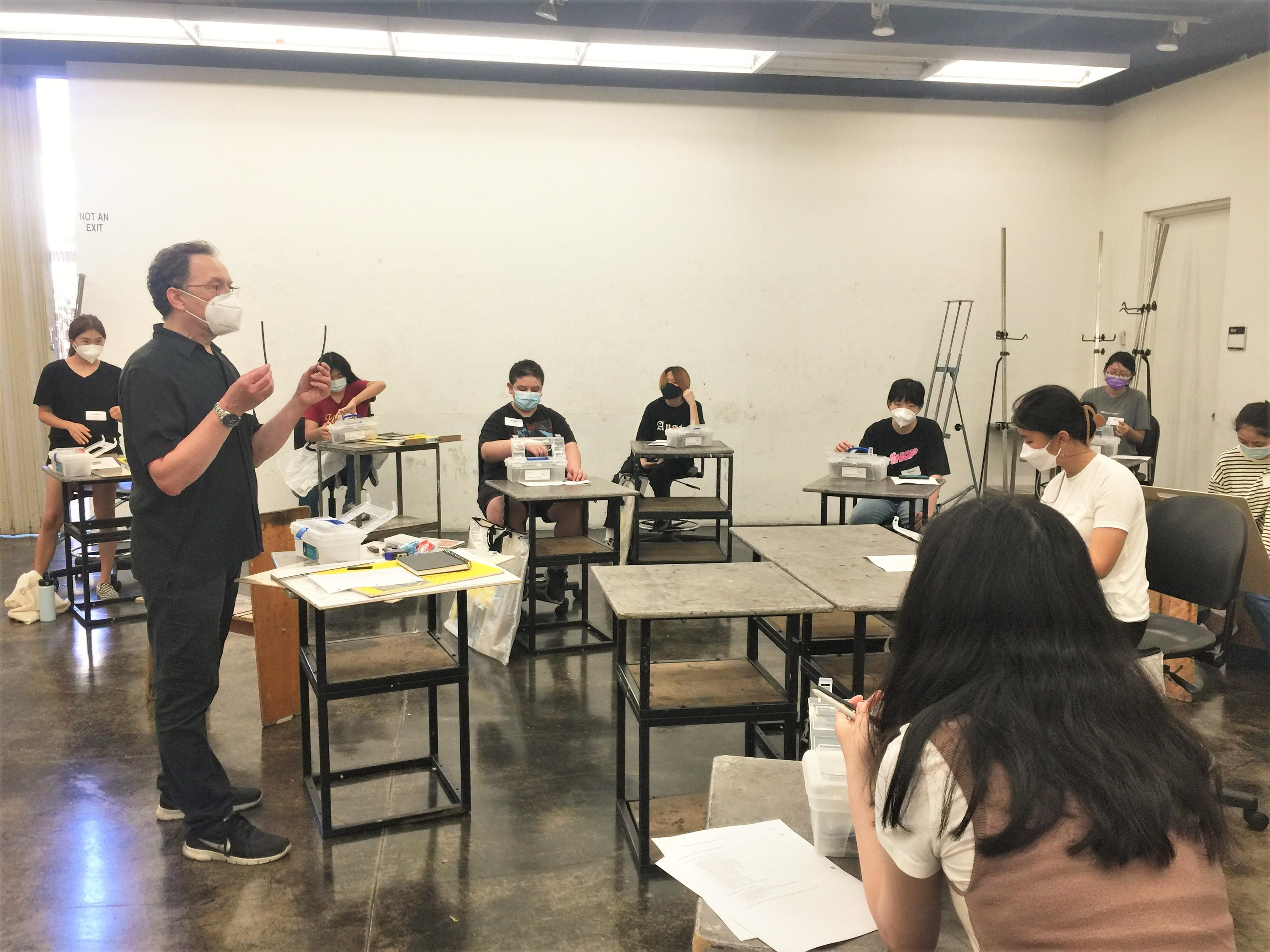 Master Teaching Artist Ira Korman reviewing art supplies to students on the first day of Ryman Arts class